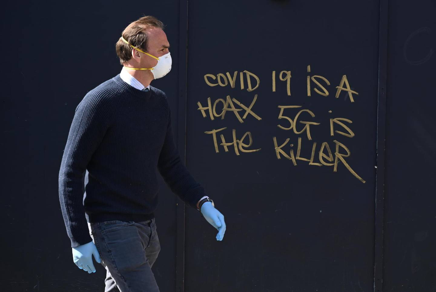 epa08362131 A man in a mask passes 5G conspiracy graffiti in London, Britain, 14 April 2020. A number of social media accounts are creating conspiracy theories about links between 5G technology and coronavirus. Countries around the world are taking increased measures to stem the widespread of the SARS-CoV-2 coronavirus which causes the Covid-19 disease.  EPA/NEIL HALL