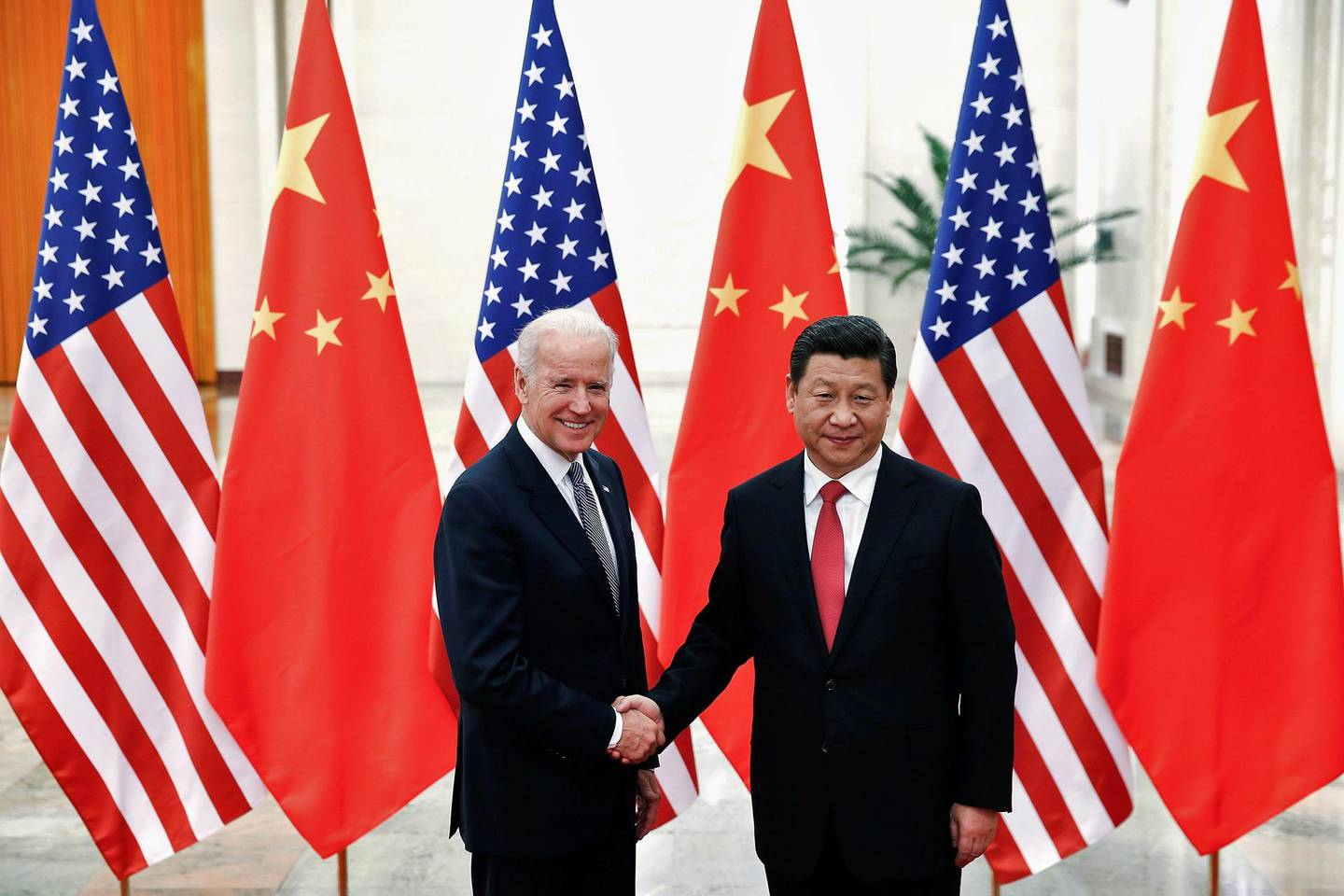 FILE PHOTO: Chinese President Xi Jinping shakes hands with U.S. Vice President Joe Biden (L) inside the Great Hall of the People in Beijing December 4, 2013. REUTERS/Lintao Zhang/Pool/File Photo