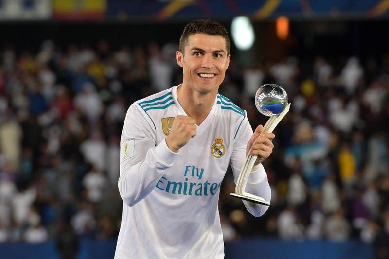 TOPSHOT - Real Madrid's Portuguese forward Ronaldo celebrates with the 2017 FIFA Club World Cup Silver Ball award following their victory in the Club World Cup final football match against Gremio at Zayed Sports City Stadium in the Emirati capital Abu Dhabi on December 16, 2017. Real Madrid defeated Gremio 1-0 to lift the FIFA Club World Cup for the third time in their history. / AFP PHOTO / Giuseppe CACACE