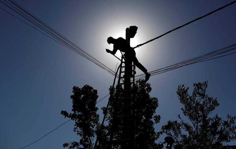 FILE PHOTO: An Iraqi technician works on an electricity pole damaged during fighting between Iraqi forces and Islamic state fighters, in eastern Mosul, Iraq April 26, 2017. REUTERS/Danish Siddiqui/File Photo