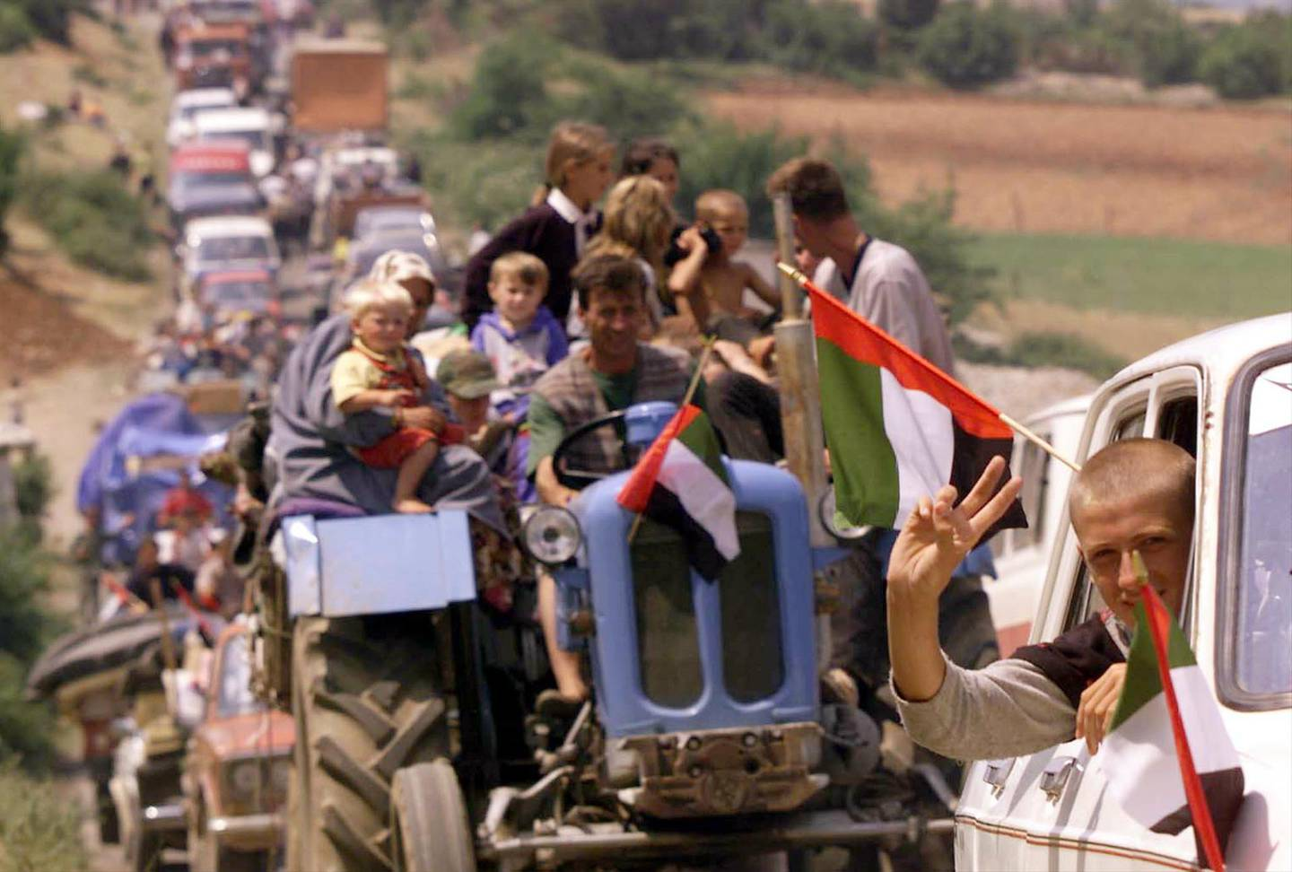 Thousands of refugees backed up for miles make their way across the border from Albania into Kosovo Wednesday June 16, 1999. There are more than 120,000 refugees in the Kukes area and thousands began heading home after weeks living in exile despite NATO and UNHCR warnings that their security is still not assured in Kosovo.  Flags are of the United Arab Emirates, who ran a refugee camp and contributed to the humanitarian aid effort in Albania. (AP Photo/David Guttenfelder)