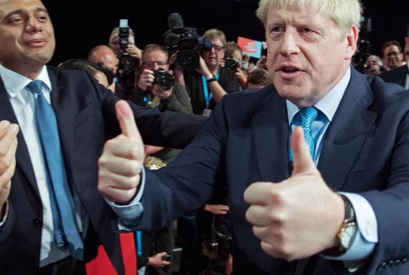 """TOPSHOT - Britain's Prime Minister Boris Johnson (R) acknowledges the applause from Britain's Chancellor of the Exchequer Sajid Javid (L) and members of his cabinet as he leaves after delivering his keynote speech to delegates on the final day of the annual Conservative Party conference at the Manchester Central convention complex, in Manchester, north-west England on October 2, 2019. Prime Minister Boris Johnson was set to unveil his plan for a new Brexit deal at his Conservative party conference Wednesday, warning the EU it is that or Britain leaves with no agreement this month. Downing Street said Johnson would give details of a """"fair and reasonable compromise"""" in his closing address to the gathering in Manchester, and would table the plans in Brussels the same day. / AFP / POOL / Stefan Rousseau"""
