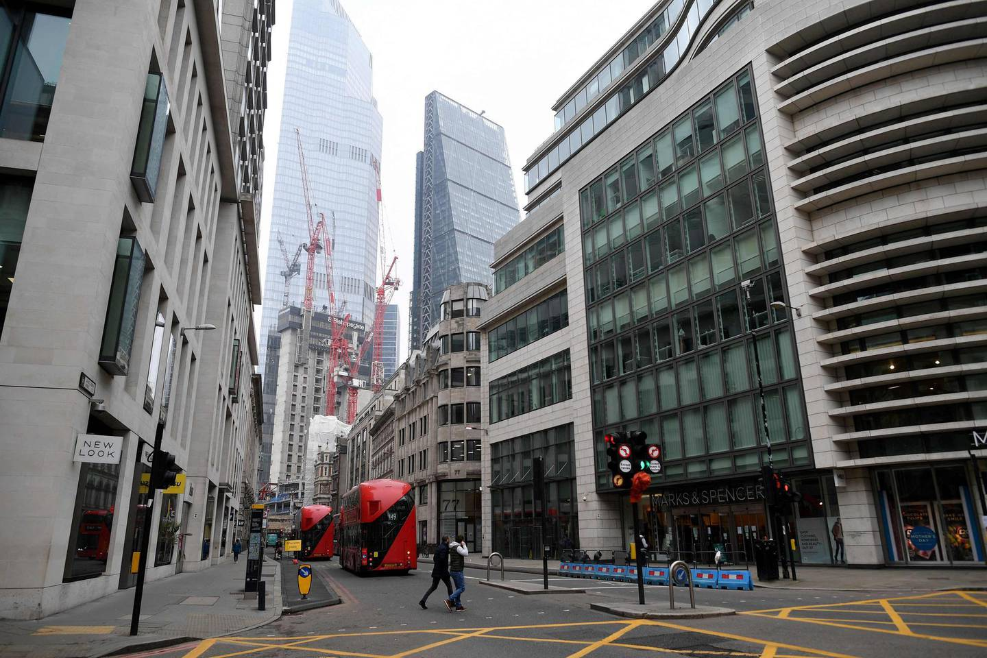 Pedestrians cross a near-deserted street in the City of London, on March 2, 2021, as the 50-storey office tower development of 8 Bishopsgate is seen in the background. / AFP / JUSTIN TALLIS