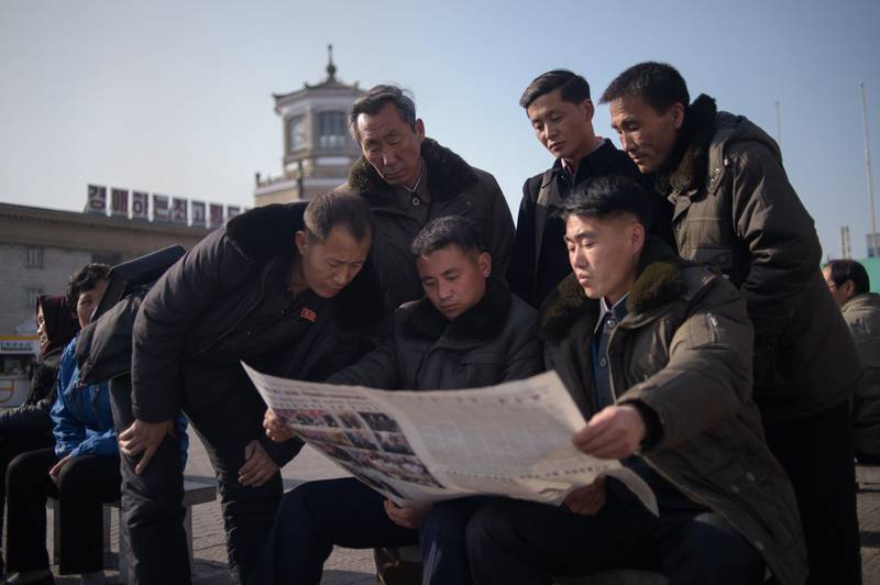 """CORRECTION / People read the Rodong Sinmun newspaper showing coverage of North Korea's leader Kim Jong Un visiting Vietnam for a summit in Hanoi with US President Donald Trump, in a public square in Pyongyang on February 28, 2019. The US-North Korea nuclear summit in Hanoi ended abruptly without a deal, with President Donald Trump saying he had decided to """"walk"""" in the face of Kim Jong Un's demands to drop sanctions.  / AFP / Kim Won Jin"""