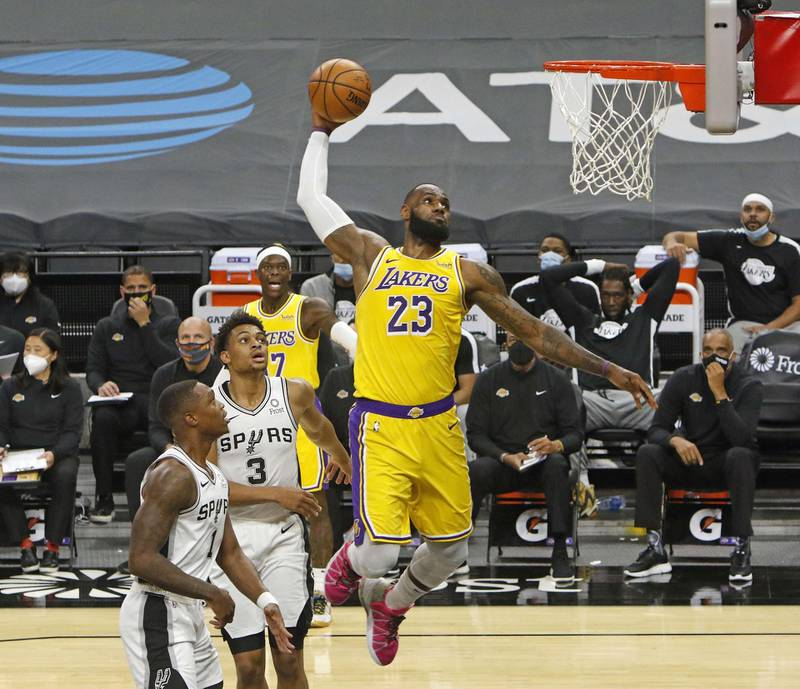SAN ANTONIO, TX - DECEMBER 30 LeBron James #23 of the Los Angeles Lakers dunks past spurs defenders during first half action at AT&T Center on December 30, 2020 in San Antonio, Texas. NOTE TO USER: User expressly acknowledges and agrees that , by downloading and or using this photograph, User is consenting to the terms and conditions of the Getty Images License Agreement.   Ronald Cortes/Getty Images/AFP == FOR NEWSPAPERS, INTERNET, TELCOS & TELEVISION USE ONLY ==