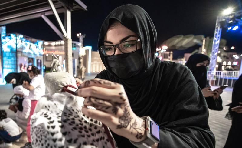 Abu Dhabi, United Arab Emirates, November 23, 2020.   Sheikh Zayed Heritage Festival celebrations at Al Wathba.  Zainab Ali Abedelnabi, ties the hood of the falcon.Victor Besa/The NationalReporter:  Samia BadihSection:  NAFor:  Standalone/Stock