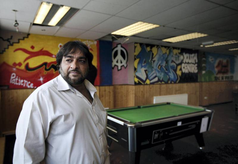 Hanif Qadir, a former extremist who now runs the Active Change Foundation, a de-radicalization project in London which works with young people at risk of embracing terrorism and people convicted of terrorists offenses, stands at the foundation's youth centre, in east London, Monday, May 23, 2011. In Britain, a controversial government project involving police and educators has identified 1,000 people, most aged under 25 but some as young as 7-years-old, as vulnerable to the appeal of extremism _ many of whom reguarly browse jihadist videos or websites. Youngsters swap imported extremists DVDs and clips of beheadings stored on their cellphones, and use SMS messages or Twitter to trade addresses for jihdaist websites, Qadir said.(AP Photo/Lefteris Pitarakis)