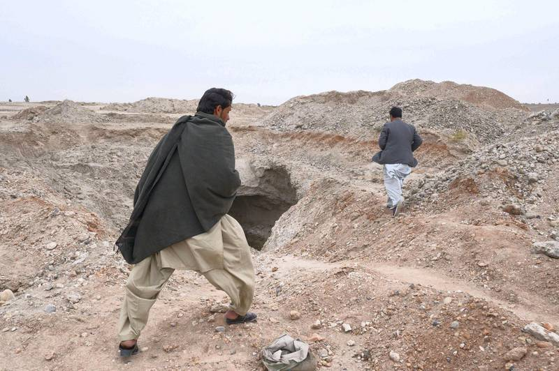 Men walk past an underground river near Gereshk, Helmand, the same landscape scoured by scorpion hunters in the summer-time.