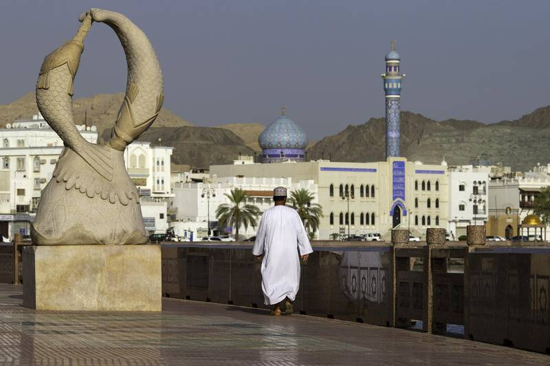An Omani man walks along the Mutrah Corniche seafront lined with 19th Century merchants houses in the old city of Muscat, Oman, on Monday, May 7, 2018. Being the Switzerland of the Gulf served the country well over the decades, helping the sultanate survive, thrive and make it a key conduit for trade and diplomacy in the turbulent Middle East.Photographer: Christopher Pike/Bloomberg