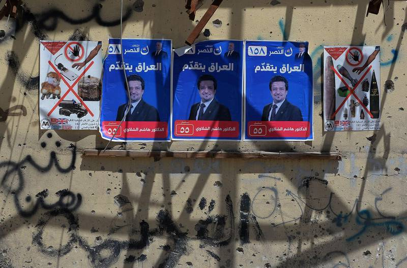 Election campaign posters are seen plastered on the wall of a destroyed building in the former embattled city of Mosul on May 1, 2018 ahead of the upcoming Iraqi parliamentary elections.  / AFP PHOTO / Zaid AL-OBEIDI