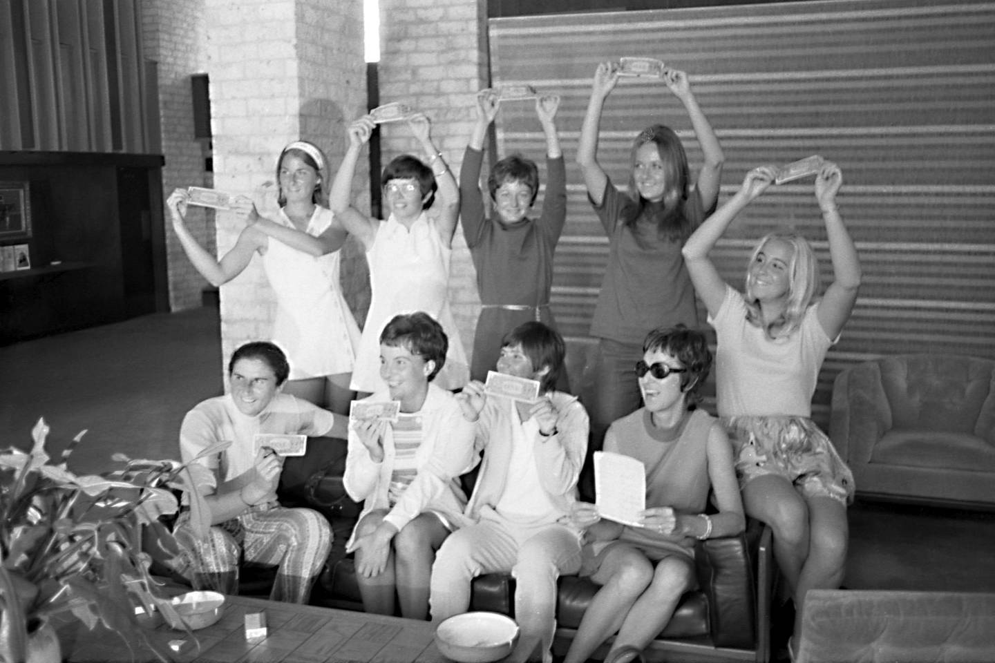 In this Sept. 23, 1970, photo provided the Houston Library, tennis players hold up $1 bills after signing a contract with World Tennis magazine publisher Gladys Heldman to turn pro and start the Virginia Slims tennis circuit. From left standing are: Valerie Ziegenfuss, Billie Jean King, Nancy Richey and Peaches Bartkowicz. From left seated are: Judy Tegart Dalton, Kerry Melville Reid, Rosie Casals, Gladys Heldman and Kristy Pigeon. Gladys Heldman replaced her daughter, Julie Heldman, who was injured and unable to pose for the 1970 photo.  It's the 50th anniversary of Billie Jean King and eight other women breaking away from the tennis establishment in 1970 and signing a $1 contract to form the Virginia Slims circuit. That led to the WTA Tour, which offers millions in prize money. (Bela Ugrin/Courtesy Houston Library via AP)