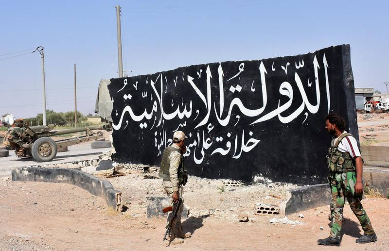 """Syrian pro-government forces set up a road checkpoint next to a mural reading the Arabic: """"Islamic State"""" after they took control of the northern Syrian town of Maskanah from the jihadists on June 5, 2017.  / AFP PHOTO / George OURFALIAN"""