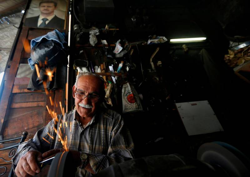 A Syrian man works in his metal workshop beneath a portrait of Syrian President Bashar al-Assad in old Damascus, on June  16, 2020. The Caesar Syria Civilian Protection Act of 2019, a US law that aims to sanction any person who assists the Syrian government or contributes to the country's reconstruction, is to come into force on June 17. / AFP / LOUAI BESHARA