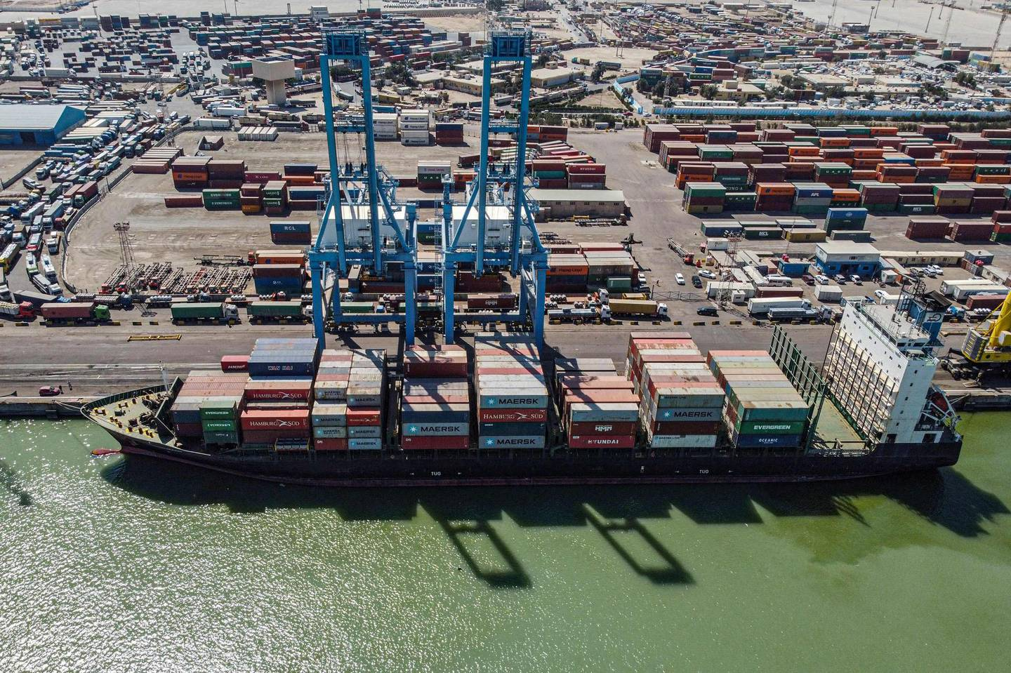 This picture taken on March 14, 2021 shows an aerial view of containers being unloaded off a cargo ship moored at the port of Umm Qasr, south of Iraq's southern city of Basra. Iraq is ranked the 21st most corrupt country by Transparency International. In January, the advocacy group said public corruption had deprived Iraqis of basic rights and services, including water, health care, electricity and jobs. It said systemic graft was eating away at Iraqis' hopes for the future, pushing growing numbers to try to emigrate. In 2019, hundreds of thousands of protesters flooded Iraqi cities, first railing against poor public services, then explicitly accusing politicians of plundering resources meant for the people. / AFP / Hussein FALEH