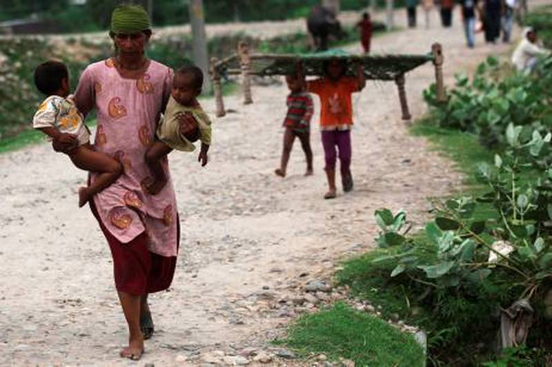 Indian villagers carry their belongings during a flash flood of the Tawi river on the outskirts of Jammu on August 4, 2012. Some 27 people, including 19 workers at a power plant, are missing following flash floods triggered by heavy rains in three northern Indian states, officials said. AFP PHOTO/ STR  *** Local Caption ***  155258-01-08.jpg