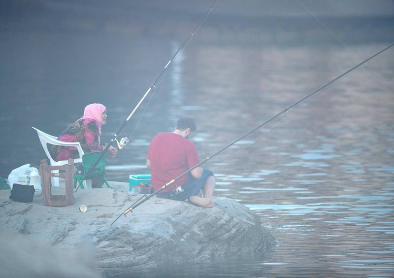 A couple goes fishing amidst the fog at the Yas Iron Bridge area in Abu Dhabi on June 4th, 2021. Victor Besa / The National.
