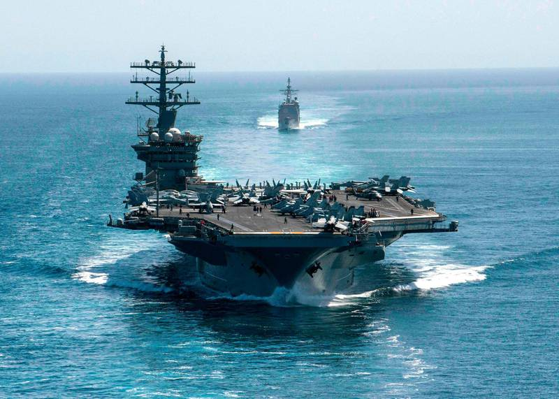"""This handout photo courtesy of US Navy shows the aircraft carrier USS Nimitz (front) and the guided-missile cruiser USS Philippine Sea during a Strait of Hormuz transit on September 18, 2020. Iran's Foreign Minister Mohammad Javad Zarif on December 31, 2020, accused US President Donald Trump of aiming to fabricate a """"pretext for war"""" as tensions mount between the two countries. His remarks come ahead of the first anniversary of the US killing of top Iranian military commander Qasem Soleimani in a drone strike in Baghdad on January 3. The Nimitz has been patrolling Gulf waters since late November 2020 and two US B-52 bombers recently overflew the region on December 30. - RESTRICTED TO EDITORIAL USE - MANDATORY CREDIT """"AFP PHOTO / US NAVY /  Petty Officer 3rd Class Elliot Schaudt"""" - NO MARKETING - NO ADVERTISING CAMPAIGNS - DISTRIBUTED AS A SERVICE TO CLIENTS  / AFP / US NAVY / US NAVY / US NAVY / elliot Schaudt / RESTRICTED TO EDITORIAL USE - MANDATORY CREDIT """"AFP PHOTO / US NAVY /  Petty Officer 3rd Class Elliot Schaudt"""" - NO MARKETING - NO ADVERTISING CAMPAIGNS - DISTRIBUTED AS A SERVICE TO CLIENTS"""