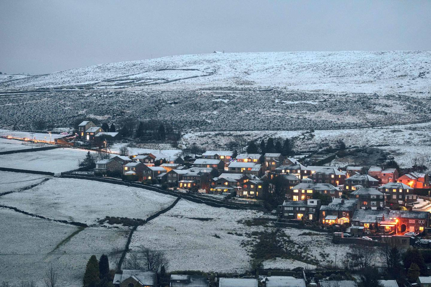 Snow-covered homes are illuminated at dusk in the village of Marsden, near Manchester in northern England on December 4, 2020. / AFP / OLI SCARFF