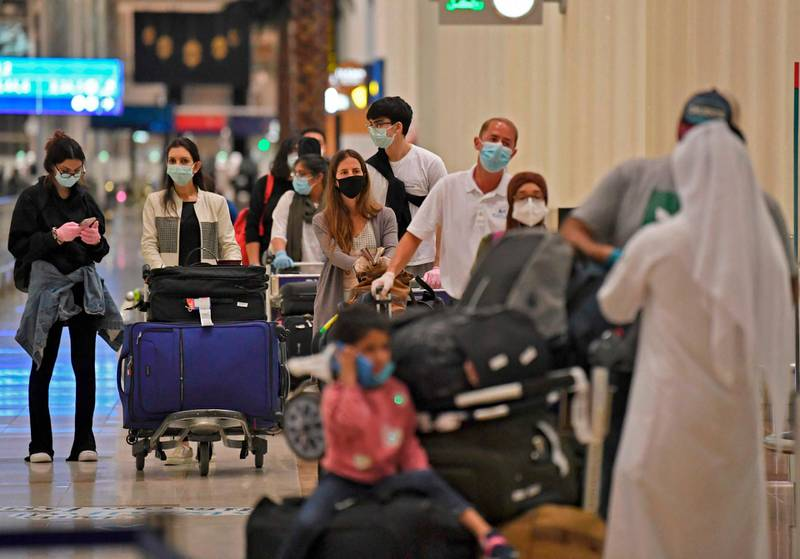 Passengers from an Emirates Airlines flight from London line up before being checked by health workers at Dubai International Airport on May 8, 2020 amid the coronavirus Covid-19 pandemic.         / AFP / Karim SAHIB