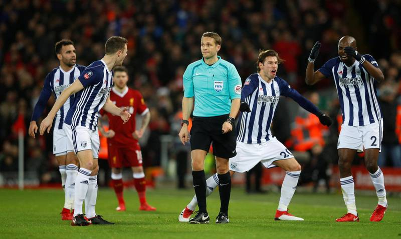 Soccer Football - FA Cup Fourth Round - Liverpool vs West Bromwich Albion - Anfield, Liverpool, Britain - January 27, 2018   West Bromwich Albion players remonstrate with referee Craig Pawson after he asks for VAR (Video Assistant Referee) after a challenge West Bromwich Albion's Jake Livermore on Liverpool's Mohamed Salah in the penalty area before awarding a penalty to Liverpool   REUTERS/Phil Noble