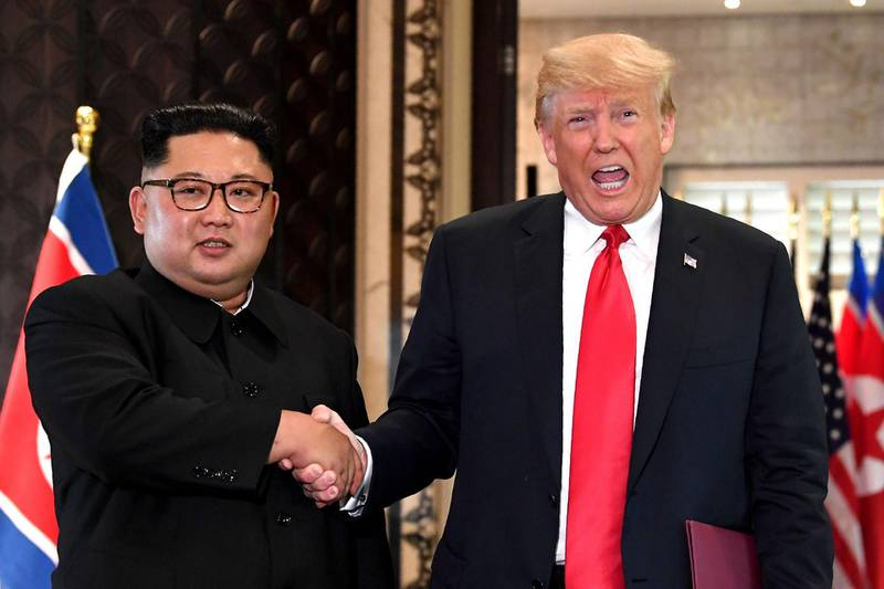 """(FILES) In this file photo taken on June 12, 2018, US President Donald Trump (R) and North Korea's leader Kim Jong Un shake hands following a signing ceremony during their historic US-North Korea summit, at the Capella Hotel on Sentosa island in Singapore.  North Korea has condemned the United States over its latest sanctions measures, warning the policy could """"block the path to denuclearization on the Korean peninsula forever"""". The warning from the North on Sunday, December 16, 2018 came days after the US said it was imposing sanctions on three senior North Korean officials over human rights abuses.  / AFP / SAUL LOEB"""