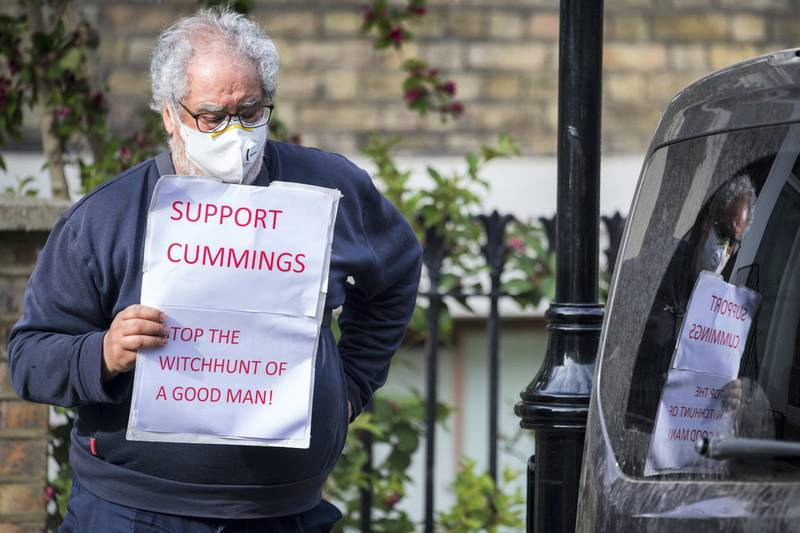 LONDON, ENGLAND - MAY 27: A supporter of the Chief Advisor to Prime Minister Boris Johnson, Dominic Cummings, waits for him to leave his home on May 27, 2020 in London, England. On March 31st 2020, Downing Street confirmed to journalists that Dominic Cummings, senior advisor to British Prime Minister Boris Johnson, was self-isolating with COVID-19 symptoms at his home in North London. Durham police have confirmed that he was actually hundreds of miles away at his parent's house in the city, having travelled with his wife and young son. (Photo by Leon Neal/Getty Images,)
