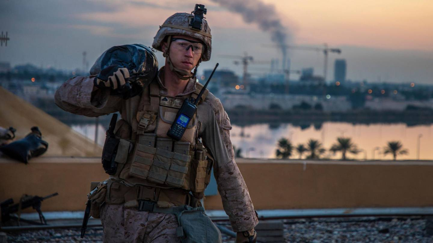 In this Saturday, Jan. 4, 2020, photo, released by the U.S. military, a U.S. Marine with 2nd Battalion, 7th Marines that is part of a quick reaction force, carries a sand bag during the reinforcement of the U.S. embassy compound in Baghdad, Iraq, Jan. 4, 2020. The blowback over the U.S. killing of a top Iranian general mounted Sunday, Jan. 5 as Iraq's Parliament called for the expulsion of American troops from the country — a move that could allow a resurgence of the Islamic State group. (U.S. Marine Corps photo by Sgt. Kyle C. Talbot via AP)