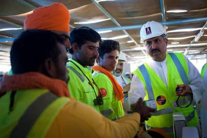 Dubai, United Arab Emirates - January 2 2013 - The UAE Minister of Labour Saqr Ghobash Saeed Gobash hands out mobile phones to construction workers at the construction site of the Al Jalila Children's Speciality Hospital. This PR event comes after Sheikh Mohammed bin Rashid Al Maktoum's announcement that the UAE should thank and focus on the work of laborers. (Razan Alzayani / The National)