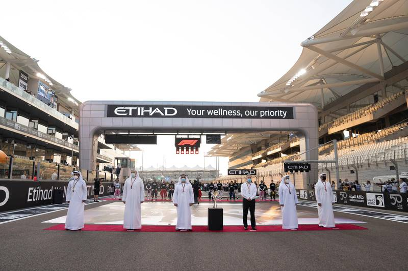 YAS MARINA, ABU DHABI, UNITED ARAB EMIRATES - December 13, 2020: HH Lt General Sheikh Saif bin Zayed Al Nahyan, UAE Deputy Prime Minister and Minister of Interior (3rd L) stands for the UAE national anthem prior to the final race of the 2020 Formula 1 Etihad Airways Abu Dhabi Grand Prix, at Yas Marina Circuit. Seen with HE Mohamed Bin Sulayem, FIA Vice President and President of the Automobile and Touring Club for the UAE (L) HE Khaldoon Khalifa Al Mubarak, CEO and Managing Director Mubadala, Chairman of the Abu Dhabi Executive Affairs Authority and Abu Dhabi Executive Council Member (2nd L) and Chase Carey, Formula 1 Chairman and CEO (4th L).  ( Hamad Al Kaabi / Ministry of Presidential Affairs ) ---