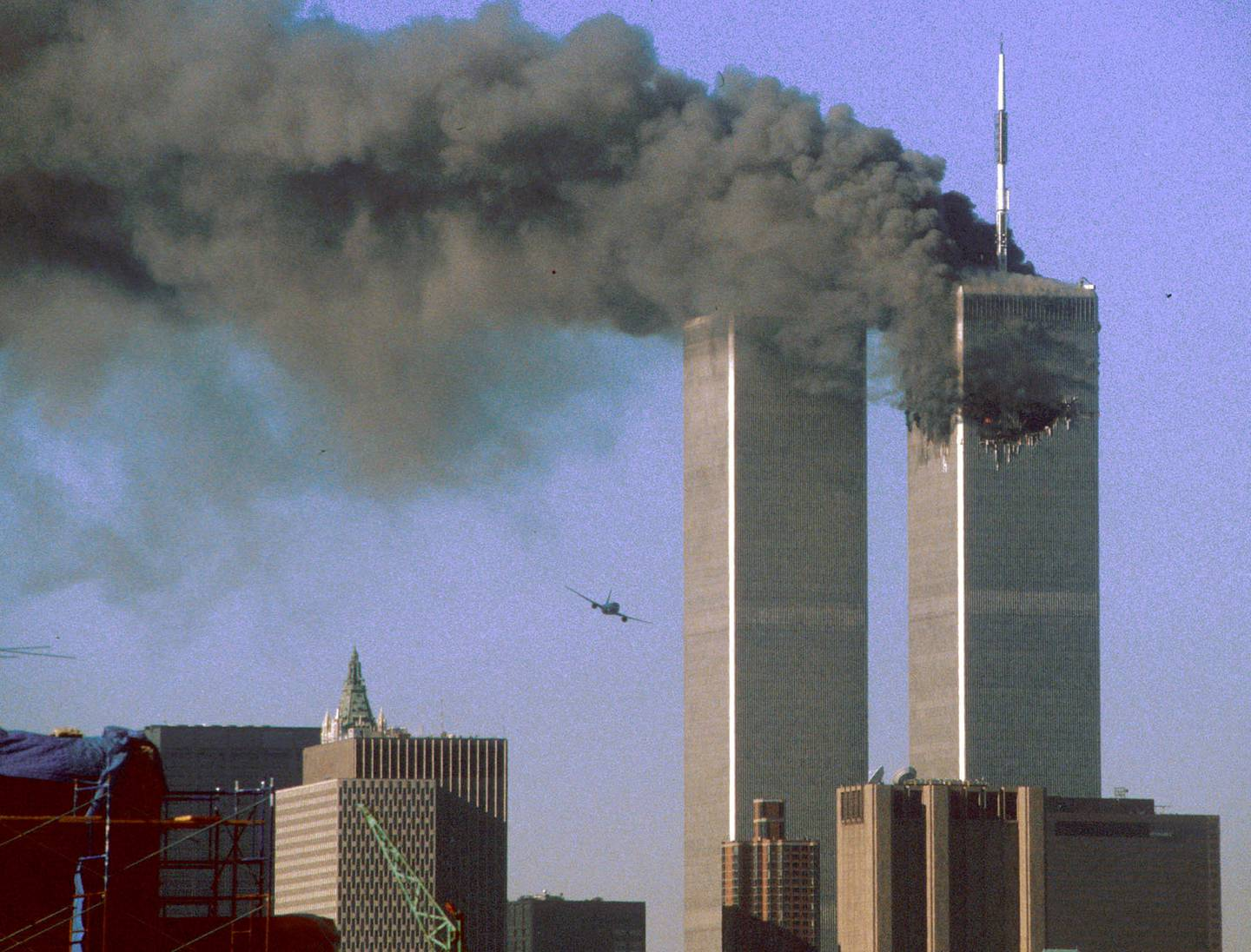 Hijacked United Airlines Flight 175 (L) flies toward the World Trade Center twin towers shortly before slamming into the south tower (L) as the north tower burns following an earlier attack by a hijacked airliner in New York City September 11, 2001. The stunning aerial assaults on the huge commercial complex where more than 40,000 people worked on an ordinary day were part of a coordinated attack aimed at the nation's financial heart. They destroyed one of America's most dramatic symbols of power and financial strength and left New York reeling. FR05070027 SECOND OF SEVEN PHOTOGRAPHS REUTERS/Sean Adair  SV