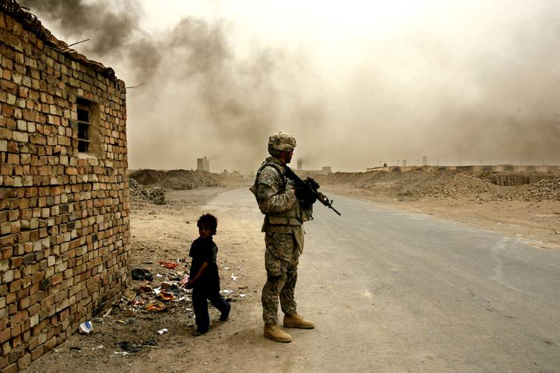 IRAQ, NARWAN - JULY 1: Iraqi child labourer, Salam (L) (6), walks past a US soldier with 4th Battalion/ 27th Field Artillery at a brick making factory on Tuesday, July 1, 2008 in Narwan, Iraq. (Photography by Warrick Page/The National)