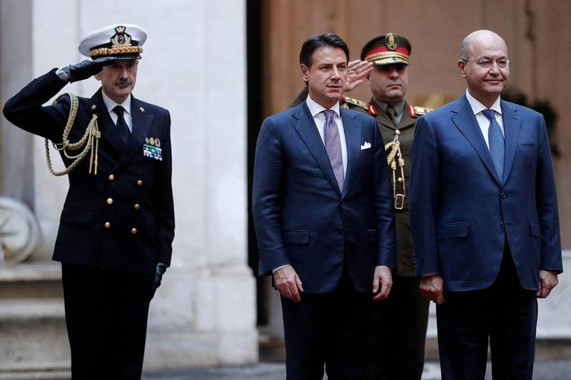 Italian Prime Minister Giuseppe Conte, third from left, is flanked by Iraqi President Barham Salih as they review the honor guard at Chigi Palace Premier office in Rome, Thursday, Nov. 22, 2018. (Riccardo Antimiani/ANSA via AP)