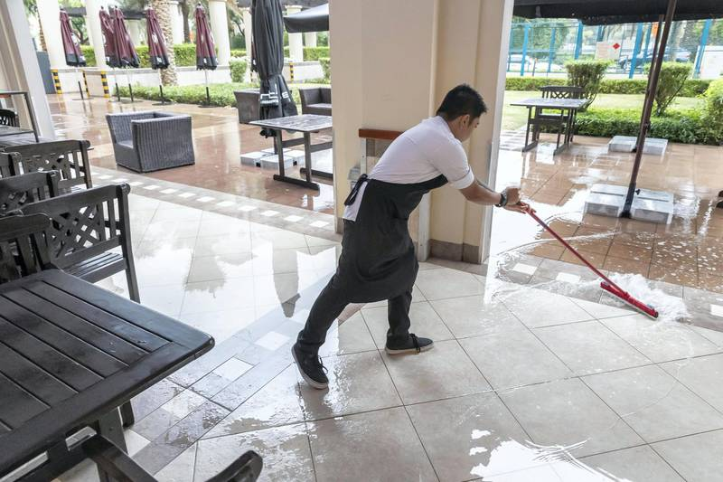 DUBAI, UNITED ARAB EMIRATES. 10 JANUARY 2020. Heavy rains in Dubai during the night had residenst wake up to wet pavements and large water puddles with some areas experiencng mild flooding. A waiter at Burts in The Greens sweeps away some water from the nights rains to get ready for the business day. (Photo: Antonie Robertson/The National) Journalist: Standalone. Section: National.