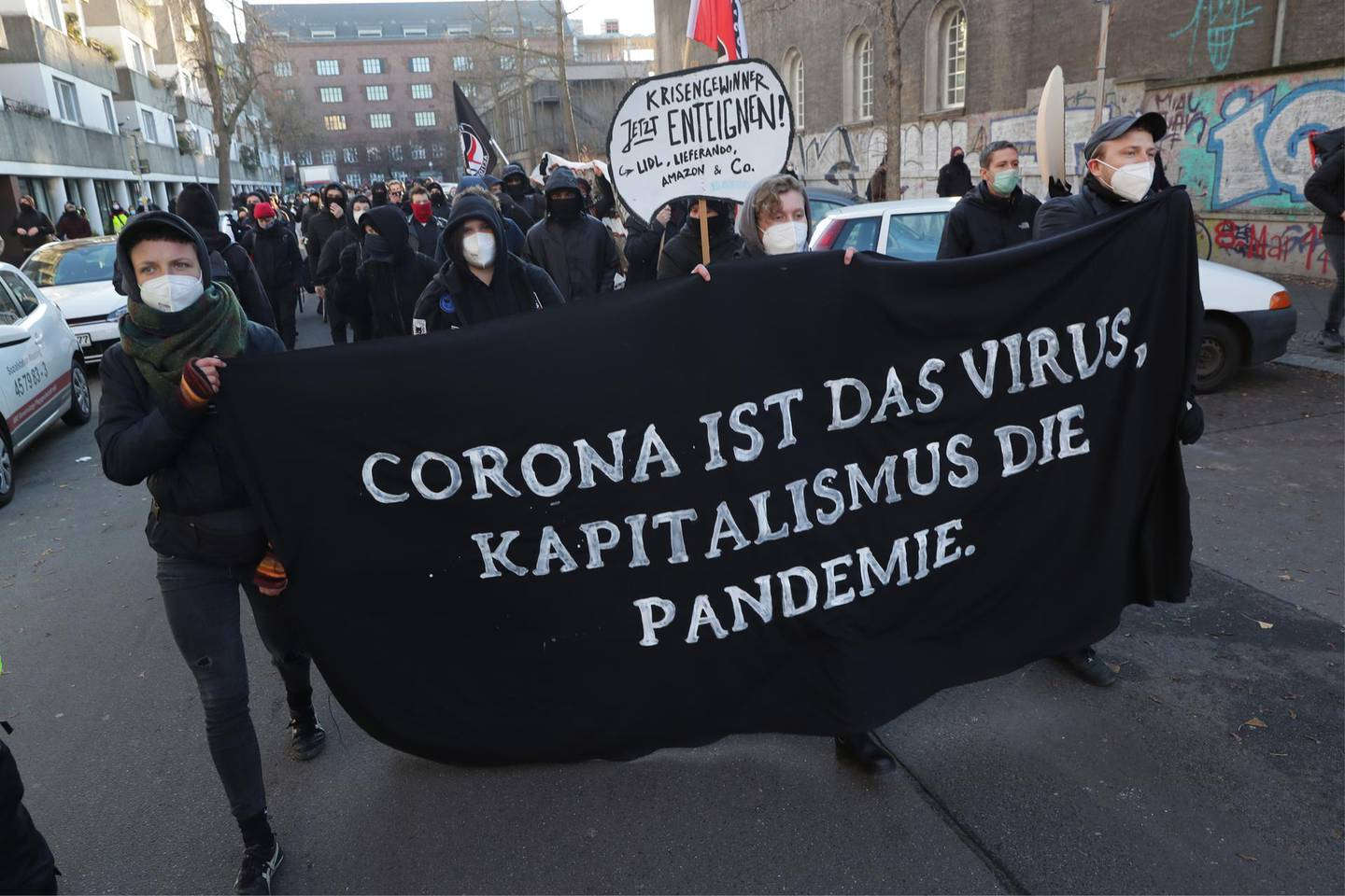 epa08911335 People participate in a demonstration 'FCK2020 - For a better tomorrow' in Berlin, Germany, 30 December 2020. Protesters are against coronavirus conspiracy ideologues and for dignified health, a fair education, labor rights and labor protection. The banner reads 'Corona is the virus, capitalism is the pandemic'.  EPA/HAYOUNG JEON