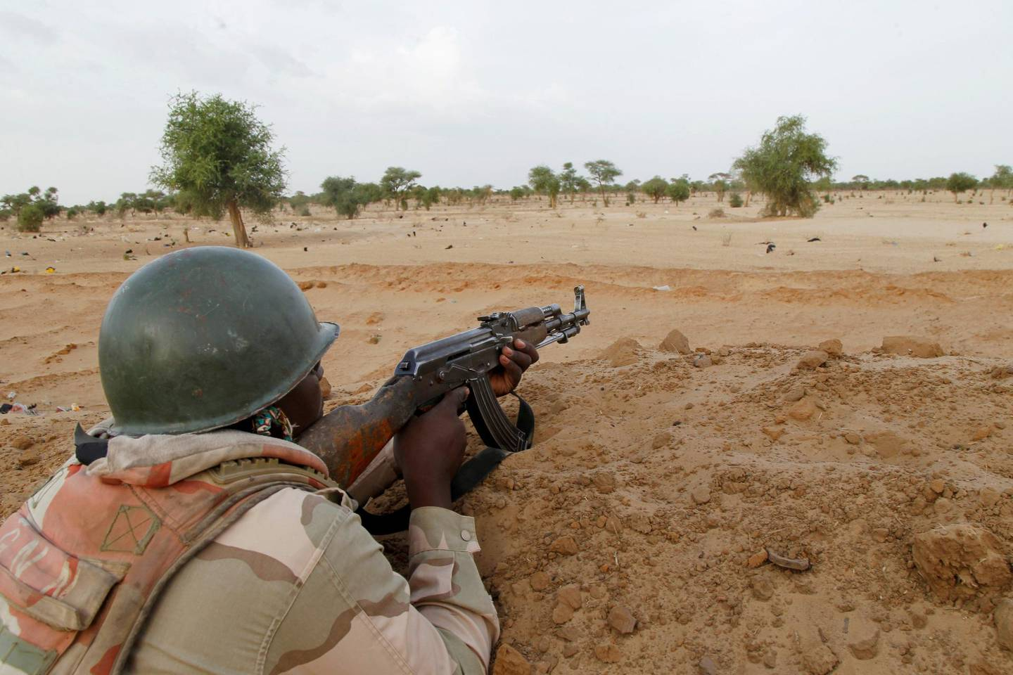 FILE PHOTO: A Niger soldier guards with his weapon pointed towards the border with neighbouring Nigeria, near the town of Diffa, Niger, June 21, 2016. Picture taken June 21, 2016. REUTERS/Luc Gnago/File Photo