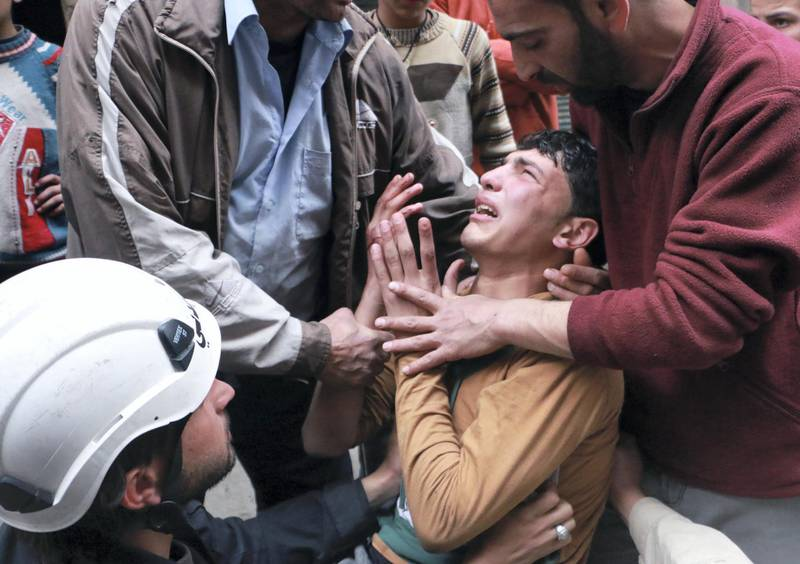 A man is comforted by a rescue worker and others following a reported air strike by government forces in which a fellow rescue worker was killed on March 9, 2014 in the northern city of Aleppo. More than 140,000 people have been killed in Syria since the start of a March 2011 uprising against the Assad family's 40-year rule AFP PHOTO / BARAA AL-HALABI (Photo by BARAA AL-HALABI / AFP)