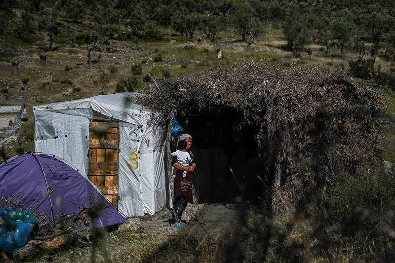 A woman with a child is pictured in a improvised tents camp near the refugee camp of Moria in the island of Lesbos on June 21, 2020. - Greece's announcement that it was extending the coronavirus lockdown at its migrant camps until July 5, cancelling plans to lift the measures on June 22, coincided with World Refugee Day on June 27, 2020. (Photo by ARIS MESSINIS / AFP)