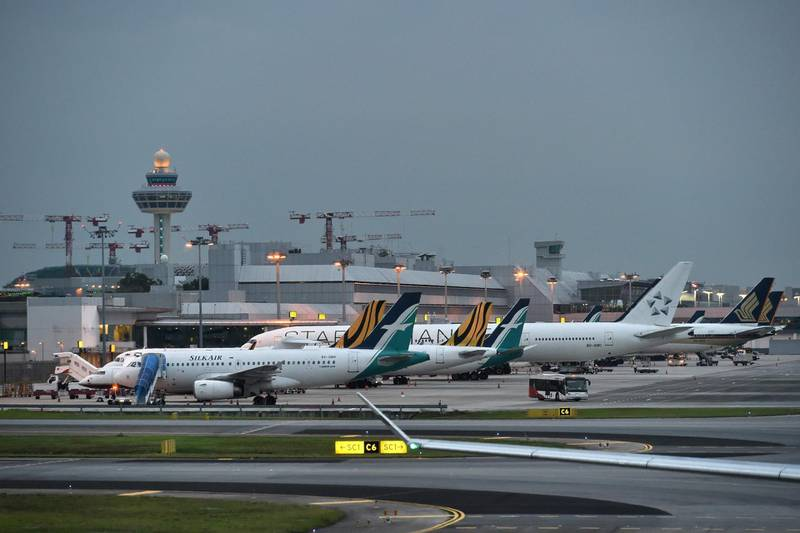 (FILES) In this file photo taken on October 31, 2017 various commercial aircraft are seen parked on the tarmac at the Changi International airport in Singapore. Singapore's aviation regulator on March 12, banned the use of Boeing 737 MAX aircraft in the country's airspace following a deadly Ethiopia plane crash at the weekend. / AFP / Roslan RAHMAN