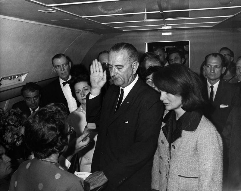 Lyndon B. Johnson taking the oath of office aboard Air Force One at Love Field Airport two hours and eight minutes after the assassination of John F. Kennedy, Dallas, Texas. Jackie Kennedy (right), still in her blood-soaked clothes, looks on. November 22, 1963. Executive Office of the President of the United States