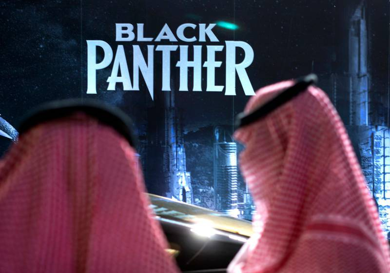 """Visitors wait in front of a """"Black Panther"""" movie banner, during an invitation-only screening, at the King Abdullah Financial District Theater, in Riyadh, Saudi Arabia, Wednesday, April 18, 2018. Saudi Arabia held a private screening of the Hollywood blockbuster """"Black Panther"""" Wednesday, to herald the launch of movie theaters that are set to open to the public next month. (AP Photo/Amr Nabil)"""