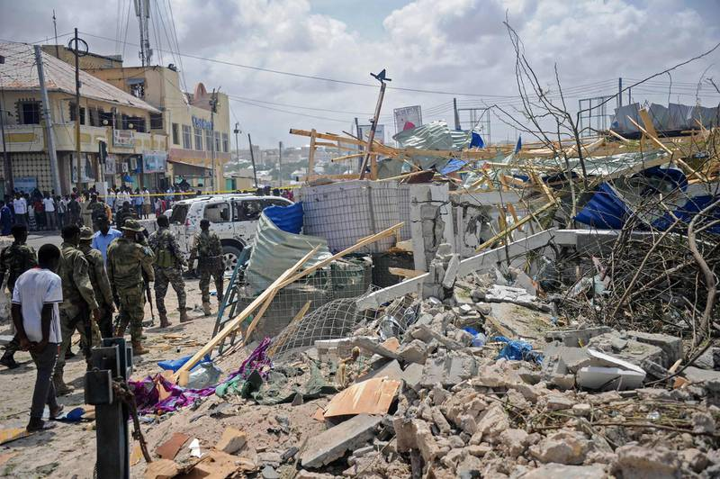 Somali security force personnel walk among debris at the site of a car bomb explosion near the building of the Interior Ministry in Mogadishu on July 7, 2018. Two explosions have rocked Somalia's internal security ministry in the capital Mogadishu, killing five civilians, a police officer said, in the latest attack claimed by Shabaab militants. / AFP / Mohamed ABDIWAHAB