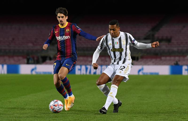 BARCELONA, SPAIN - DECEMBER 08: Trincao of Barcelona battles for possession with Alex Sandro of Juventus F.C. during the UEFA Champions League Group G stage match between FC Barcelona and Juventus at Camp Nou on December 08, 2020 in Barcelona, Spain. Sporting stadiums around Spain remain under strict restrictions due to the Coronavirus Pandemic as Government social distancing laws prohibit fans inside venues resulting in games being played behind closed doors. (Photo by David Ramos/Getty Images)