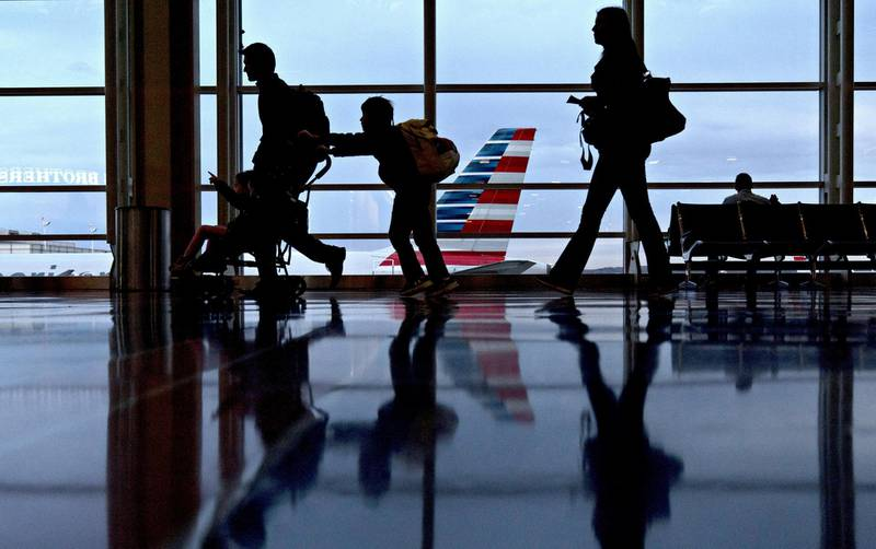 Travelers walk past an American Airlines Group Inc. aircraft at Ronald Reagan National Airport (DCA) in Washington, D.C., U.S., on Wednesday, Nov. 22, 2017. The trade association Airlines for America has projected that 28.5 million passengers will travel on U.S. airlines during the 12-day Thanksgiving air-travel period, up 3 percent from 2016. Photographer: Andrew Harrer/Bloomberg
