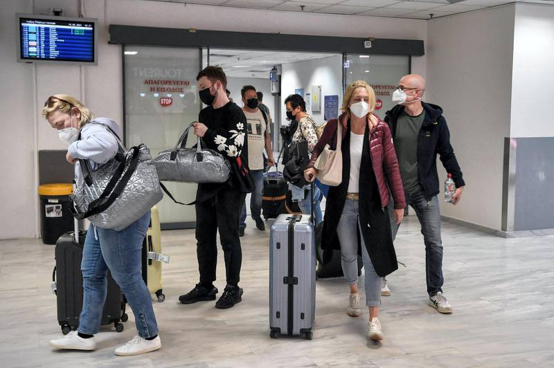 Tourists leave the international airport of Heraklion upon their arrival to spend their holidays on the island of Crete on May 14, 2021. 2021.  Greece kickstarts its tourism season on May 14, 2021, with both the government and travel operators hoping the lure of sun, sand and sea will bring a sorely needed revenue boost after last year's miserable holiday season amid the covid-19 pandemic. / AFP / Louisa GOULIAMAKI