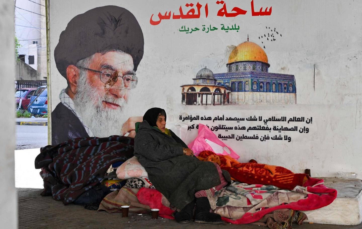 A homeless woman sits on a mattress under a poster of Iranian President Ali Khamenei and Jerusalem's Dome of the Rock shrine, in Haret Hreik, in the Lebanese capital Beirut's southern suburbs, on February 14, 2021.  / AFP / -