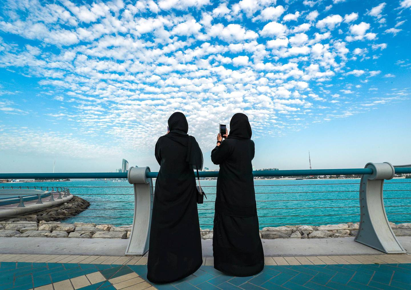 Abu Dhabi, United Arab Emirates, March 3, 2021.  Friends enjoy the view of tiny cotton ball like clouds at the Corniche before sunset. Victor Besa / The NationalSection:  NAFor:  Big Picture/Stock Images/Standalone