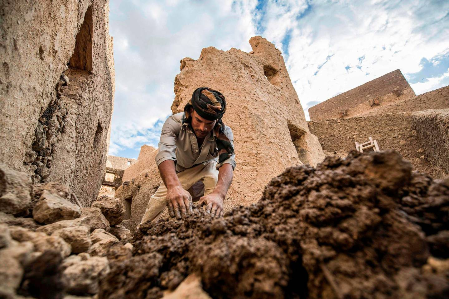 """An Egyptian labouror works on the restoration of the fortress of Shali, in the Egyptian desert oasis of Siwa, some 600 kms southwest of the capital Cairo, on November 5, 2020.  The 13th century edifice, called Shali or """"Home"""" in the Siwi language, was built by Berber populations, using kershef, a mixture of clay, salt and rock which acts as a natural insulator in an area where the summer heat can be scorching. After it was worn away by erosion, and then torrential rains in 1926, the European Union and Egyptian company Environmental Quality International (EQI) from 2018 sought to restore the building, at a cost of over $600,000.  / AFP / Khaled DESOUKI"""