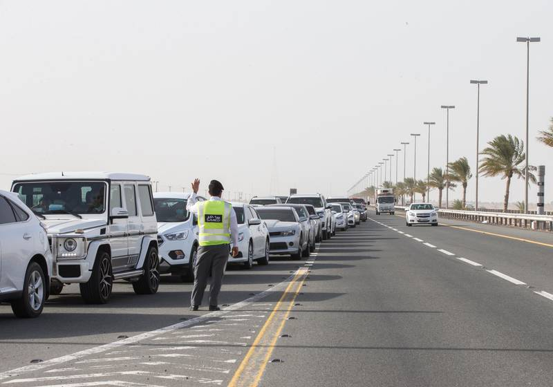 Dubai, United Arab Emirates - An officer controlling the queue to avoid traffic at the new  DPI Testing Centres border of Dubai and Abu Dhabi.  Leslie Pableo for The National for Shireena Al Nowais story