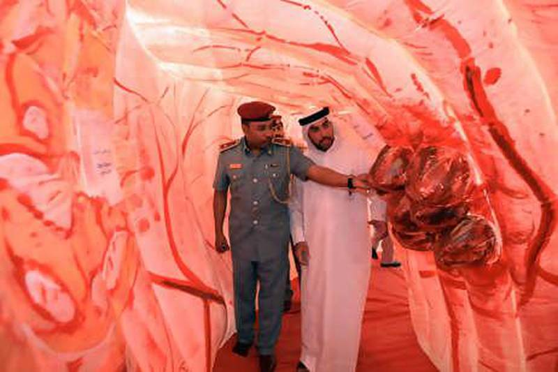 21July 2010 - Abu Dhabi - Ayman Kamel Ibrahim, Security Officer of Health Authority of Abu Dhabi and Sami Zayed Al Monzeui, community police officer, walks through a replica Colon replica at the reception at Abu Dhabi Health Authority. Ravindranath K / The National