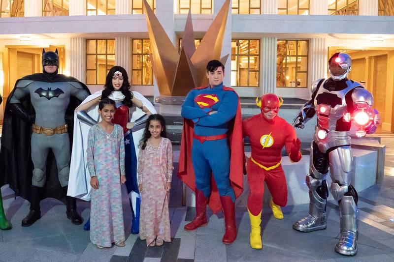 YAS ISLAND, ABU DHABI, UNITED ARAB EMIRATES - July 23, 2018: HH Sheikha Salama bint Mohamed bin Hamad bin Tahnoon Al Nahyan (L) and HH Sheikha Fatima bint Mohamed bin Hamad bin Tahnoon Al Nahyan (2nd L) stand for a photograph with super heroes during the opening of Warner Bros World Abu Dhabi.   ( Hamad Al Kaabi / Crown Prince Court - Abu Dhabi ) ---